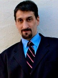 Albert Rizzi - My Blind Spot - Headshot Photo. Albert has dark hair and a dark goatee. He is wearing a navy suit with a blue shirt and a striped necktie
